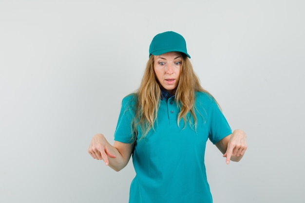 Delivery woman in t-shirt, cap pointing down and looking puzzled