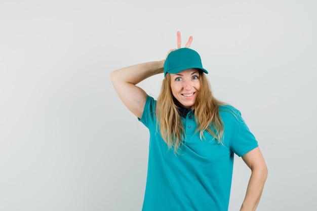 Donna delle consegne in t-shirt, cappuccio che mostra il segno v dietro la testa e sembra divertente