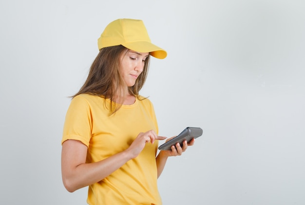 Delivery woman in t-shirt, cap using calculator and looking busy