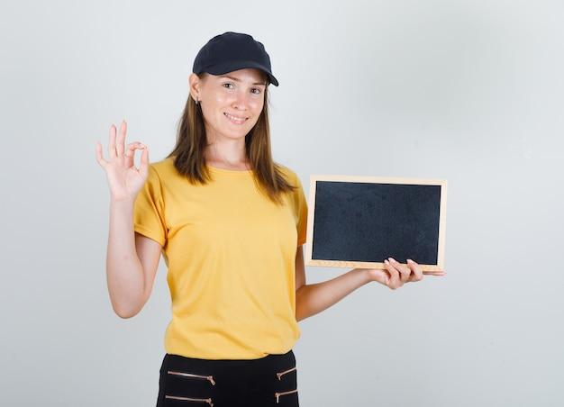 Donna di consegna in t-shirt, pantaloni, berretto che tiene lavagna con segno ok e sembra contenta