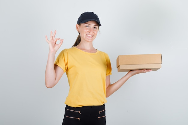 Donna di consegna in t-shirt, pantaloni, berretto che tiene la scatola di cartone con il segno giusto e che sembra soddisfatta