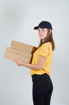 Delivery woman in t-shirt, pants, cap holding cardboard boxes and smiling .