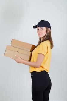 Donna di consegna in t-shirt, pantaloni, berretto con scatole di cartone e sorridente