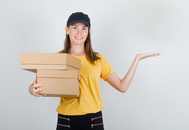 Delivery woman in t-shirt, pants, cap holding cardboard boxes and smiling