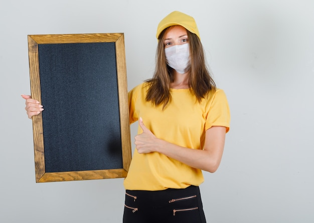 Delivery woman in t-shirt, pants, cap, mask holding blackboard with thumb up