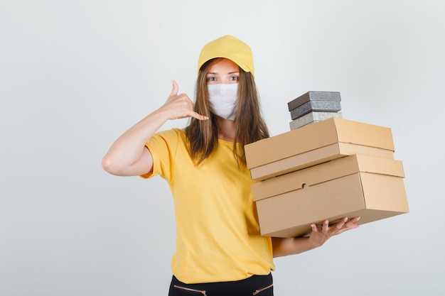 Delivery woman in t-shirt, pants, cap, mask holding boxes with phone gesture