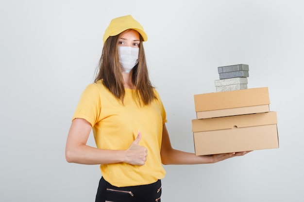 Delivery woman in t-shirt, pants, cap, mask holding boxes with thumb up and looking cheerful