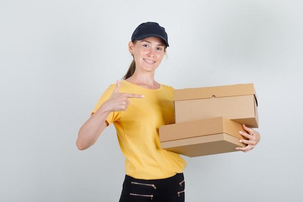 Donna di consegna in t-shirt, pantaloni, berretto che punta a scatole di cartone e sembra allegra