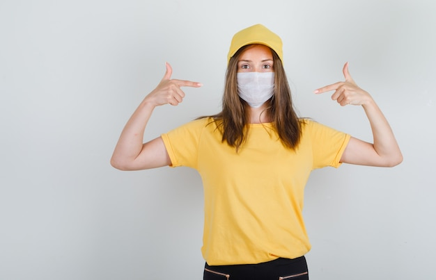 Delivery woman in t-shirt, pants, cap pointing fingers to her mask and looking careful