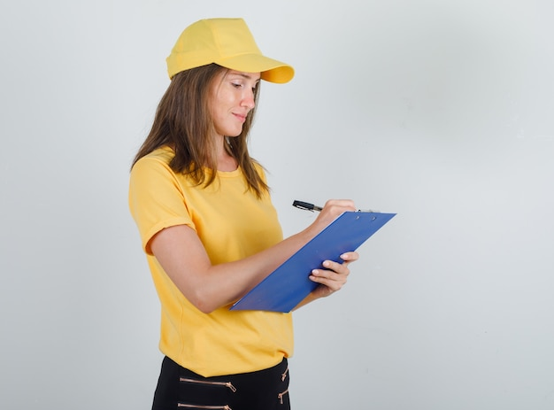 Delivery woman taking notes on clipboard in t-shirt, pants, cap and looking busy