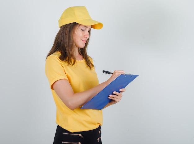 Donna di consegna prendendo appunti su appunti in t-shirt, pantaloni, berretto e guardando occupato