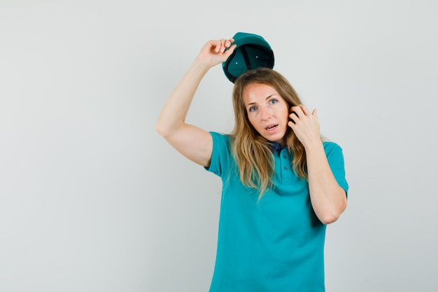 Donna di consegna che si toglie il berretto in maglietta e sembra elegante.