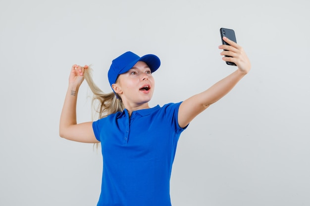 青いtシャツとキャップでストランドを保持しながら自分撮りを取っている配達の女性