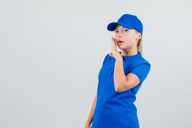 青いtシャツとキャップで口の近くの手で秘密を告げる配達の女性
