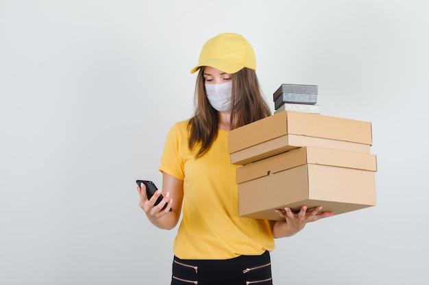 Женщина-доставщик с помощью смартфона, держа коробки в футболке, штанах, кепке и маске