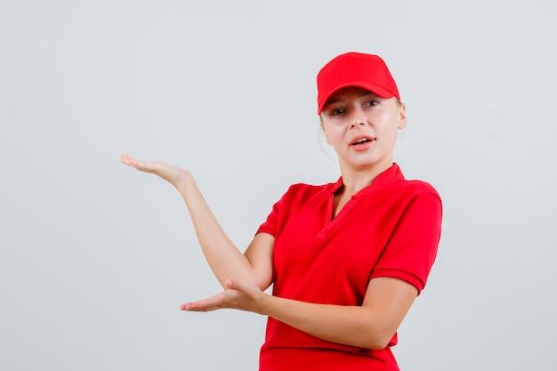 환영 또는 빨간 티셔츠와 모자에 뭔가 보여주는 배달 여자