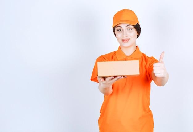 親指を上にジェスチャーするボックスを持つ配達女性
