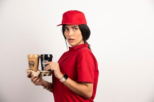 Женщина доставки с кофейными чашками, позирует на белом фоне. фото высокого качества