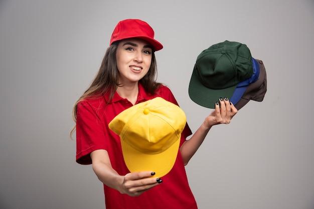 Donna delle consegne con berretti colorati regalando uno di loro.