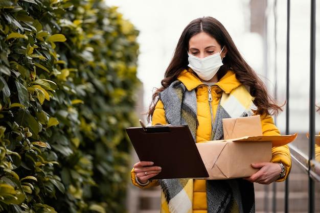 Женщина доставки с пакетом для переноски маски