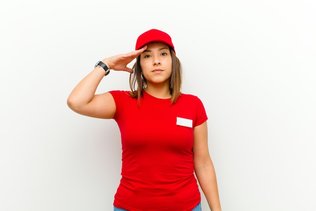 Delivery woman with a military salute in an act of honor and patriotism, showing respect