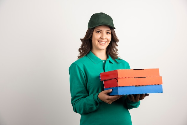 Donna di consegna con scatole per pizza in posa su bianco.