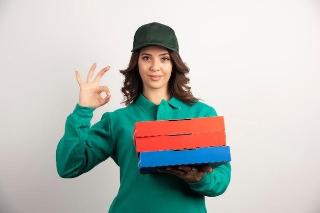 Donna di consegna con scatole per pizza in piedi su bianco.