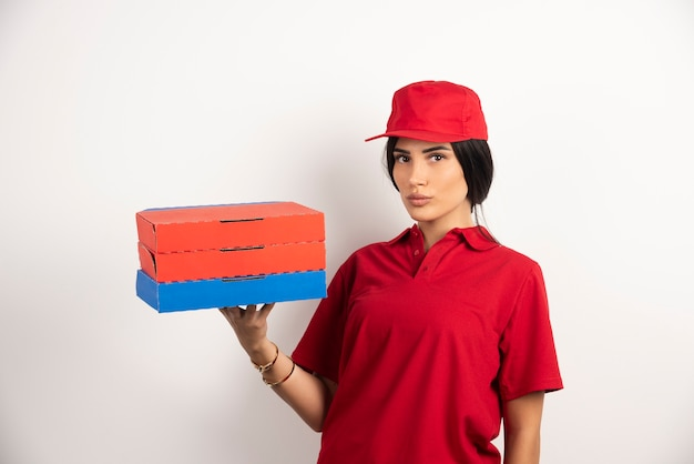 Delivery woman with pizza standing on white background.