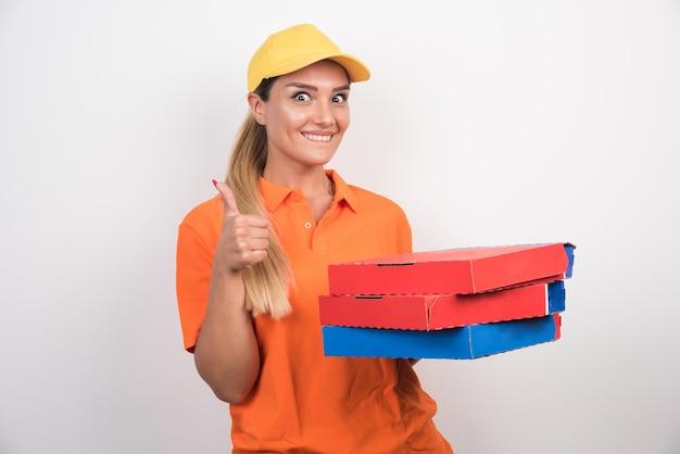 Женщина доставки с желтой шляпой, держа коробки для пиццы и делая большие пальцы руки вверх.