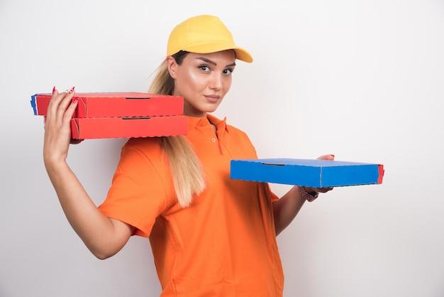 白いスペースにピザの箱を保持している黄色い帽子を持つ配達の女性