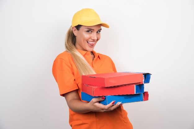 Delivery woman with yellow hat holding pizza boxes on white background.
