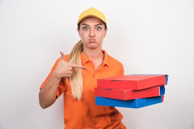 白いスペースにピザの箱を指す黄色の帽子を持つ配達の女性
