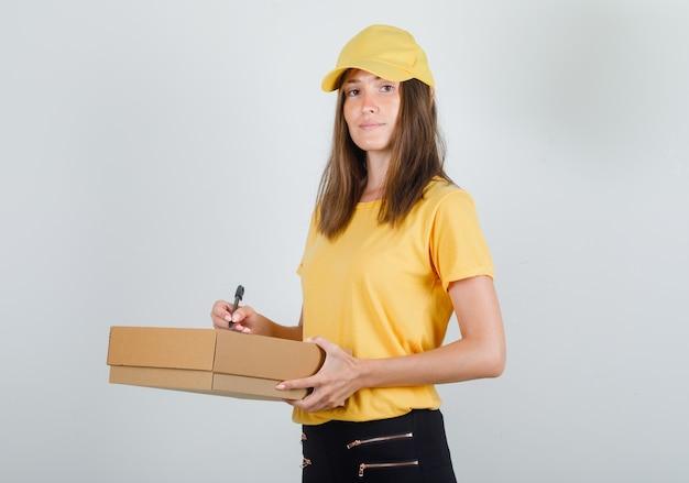 Женщина-доставщик пишет на картонной коробке и улыбается в футболке, брюках и кепке