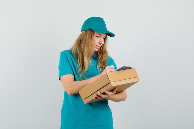 Tシャツ、キャップの段ボール箱にクリップボードに書き込み、忙しい探しの配達の女性