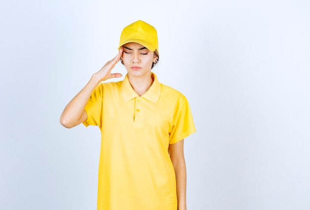 Donna delle consegne in uniforme gialla che tiene la testa con gli occhi chiusi.