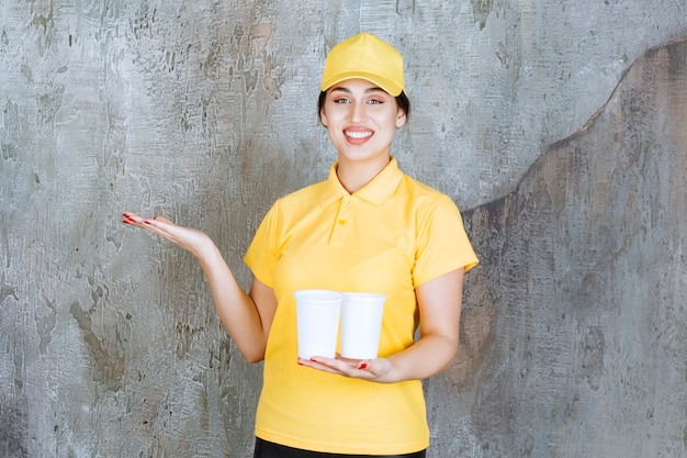 Delivery woman in yellow uniform holding two plastic cups of drink and pointing at something.
