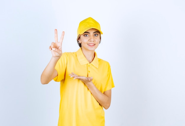 Delivery woman in yellow uniform showing two fingers and making victory sign .