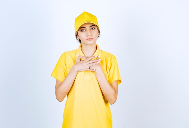 Donna di consegna in uniforme gialla in piedi e guardando seriamente la fotocamera.