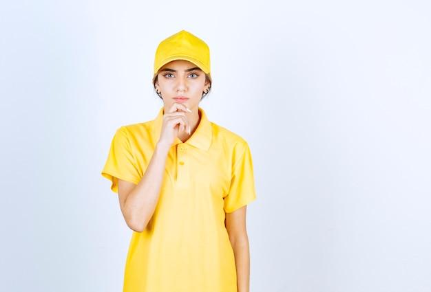 Donna di consegna in uniforme gialla in piedi e guardando la fotocamera.