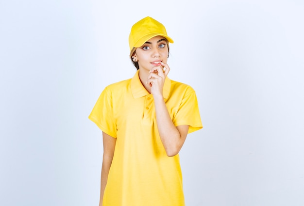 Delivery woman in yellow uniform standing and looking at camera.