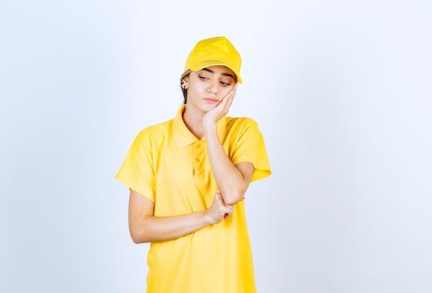Donna delle consegne in uniforme gialla in piedi e guardando in basso.