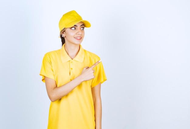 Donna delle consegne in uniforme gialla in piedi e che indica via con un dito indice.