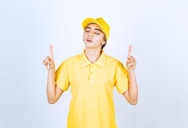 Donna delle consegne in uniforme gialla in piedi e rivolta verso l'alto con l'indice.