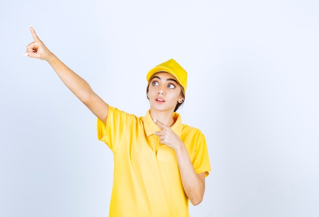 Donna delle consegne in uniforme gialla in piedi e rivolta verso l'alto.