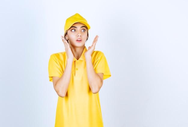 Donna di consegna in uniforme gialla in piedi e in posa.