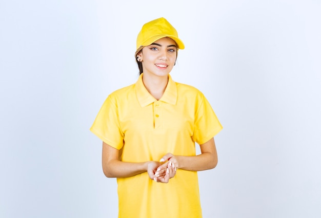 Delivery woman in yellow uniform standing and posing.
