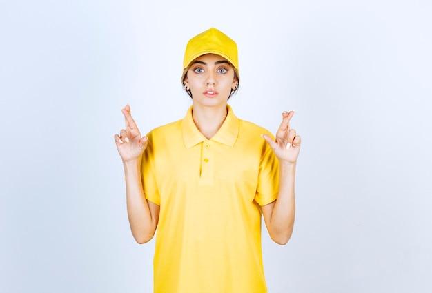 Donna di consegna in uniforme gialla in piedi e mostrando le dita incrociate.