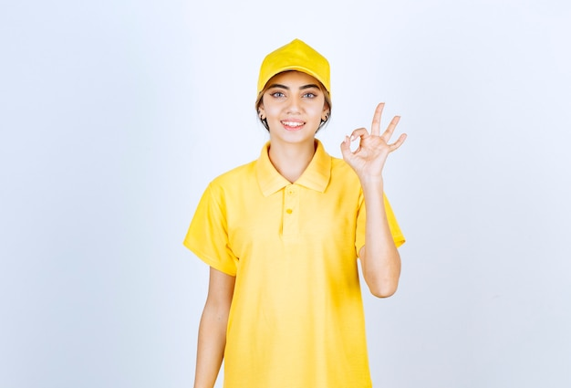 Delivery woman in yellow uniform standing and showing ok gesture .