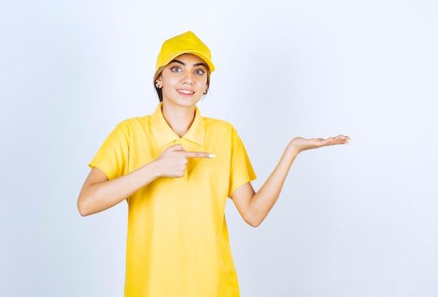 Donna delle consegne in uniforme gialla in piedi e mostrando il palmo aperto.