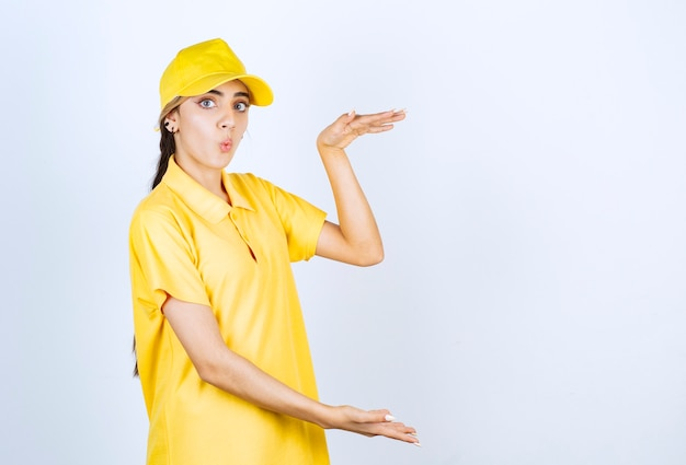 Donna delle consegne in uniforme gialla in piedi e che mostra le dimensioni con le mani.